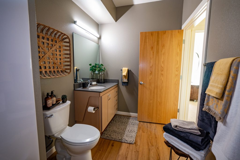 Luxury Eugene Apartments-Amazon Corner Apartments Bathroom With Wood-Style Flooring And Cabinetry And Modern Decor